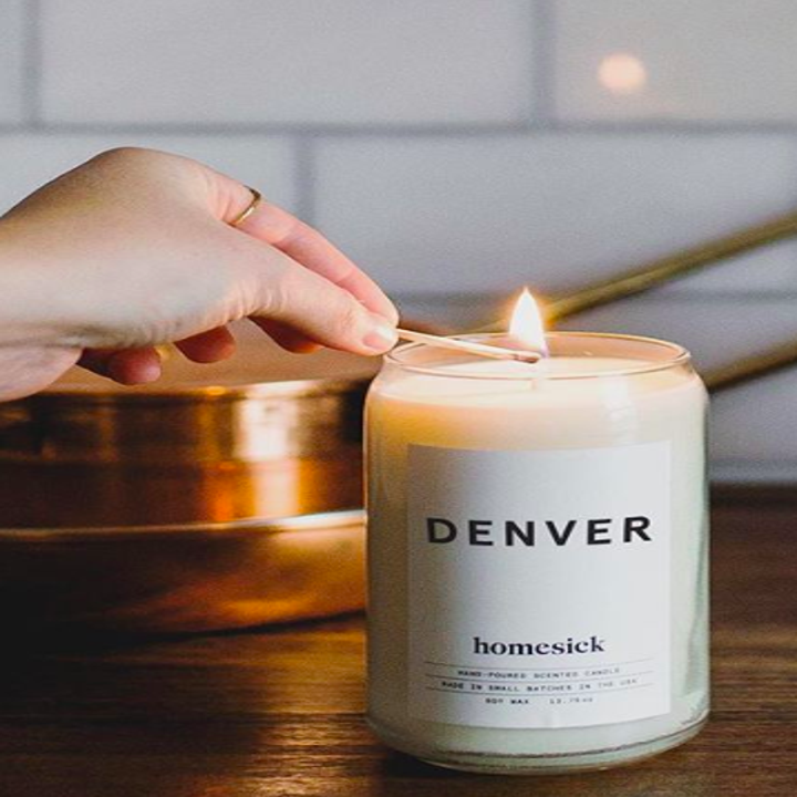 Hand lighting the Denver candle; all of their candles are white with white labels and black text and graphics