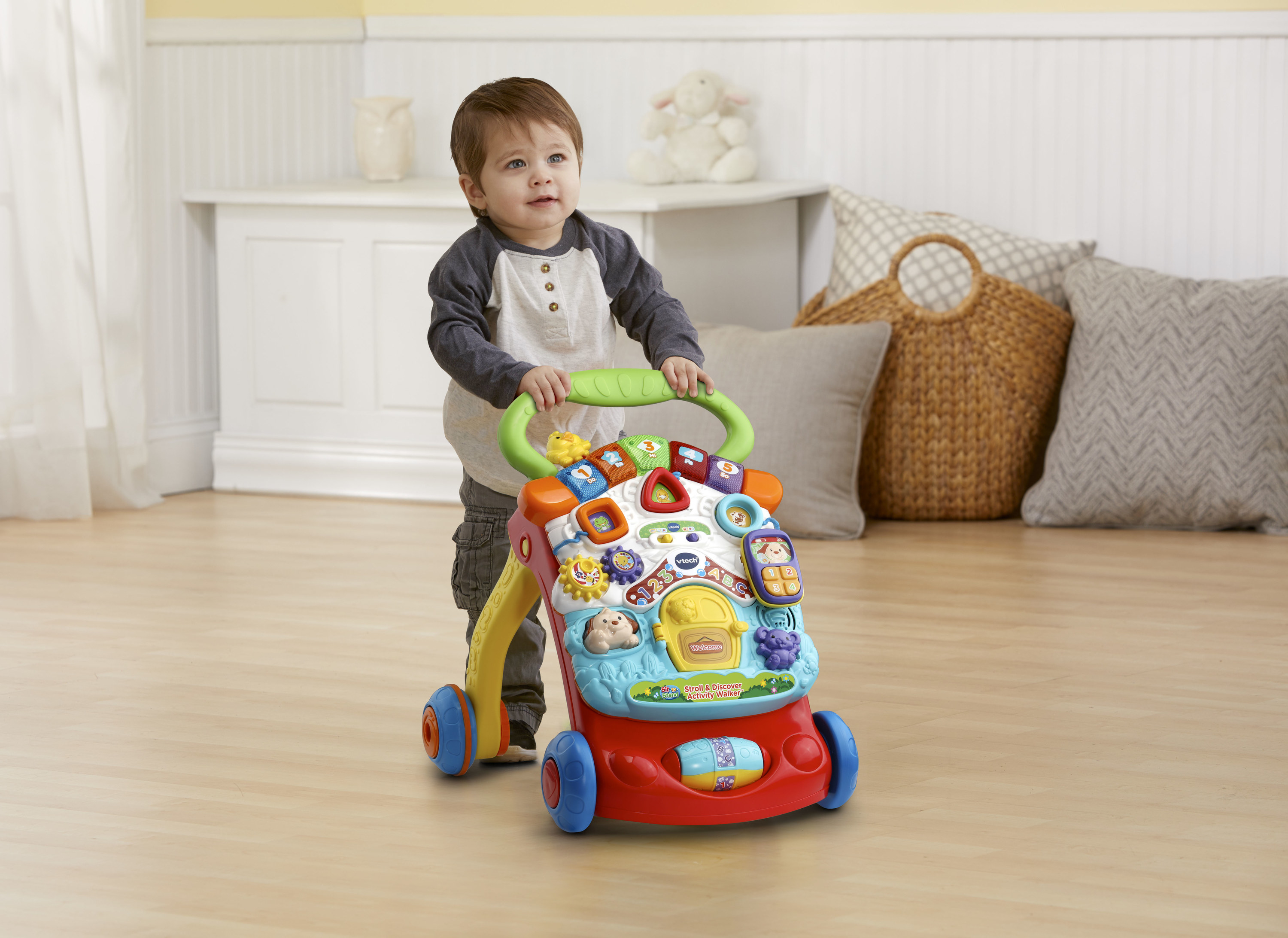 toddler using an activity walker to stroll across the living room floor