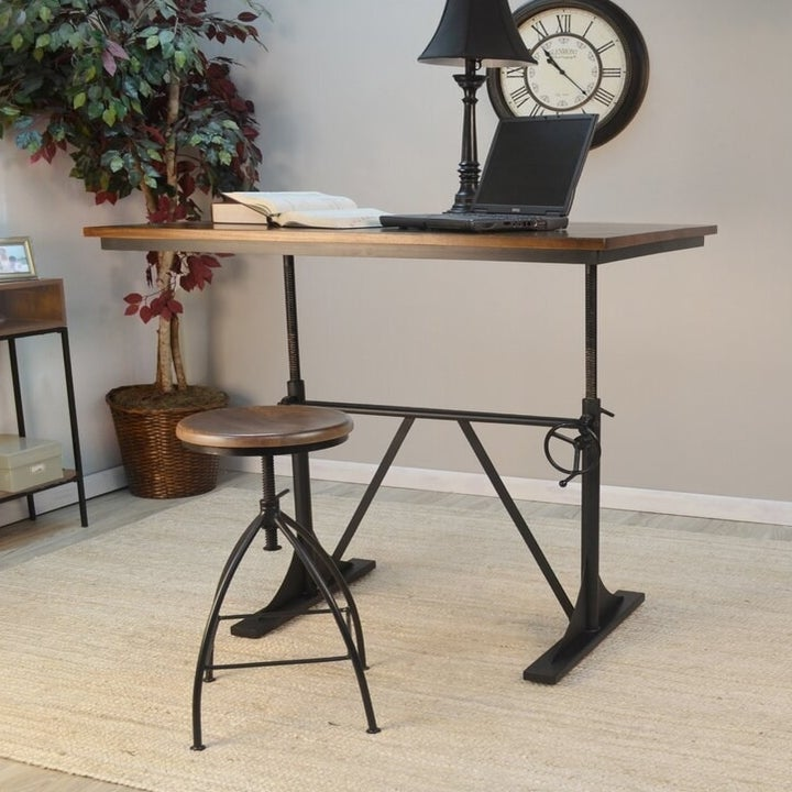 An iron and wood desk at standing height with a rustic, round supporting a laptop and lamp with a farmhouse-style round crank