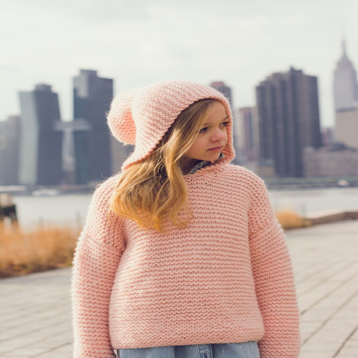 A child wearing the hokey cokey sweater in pink