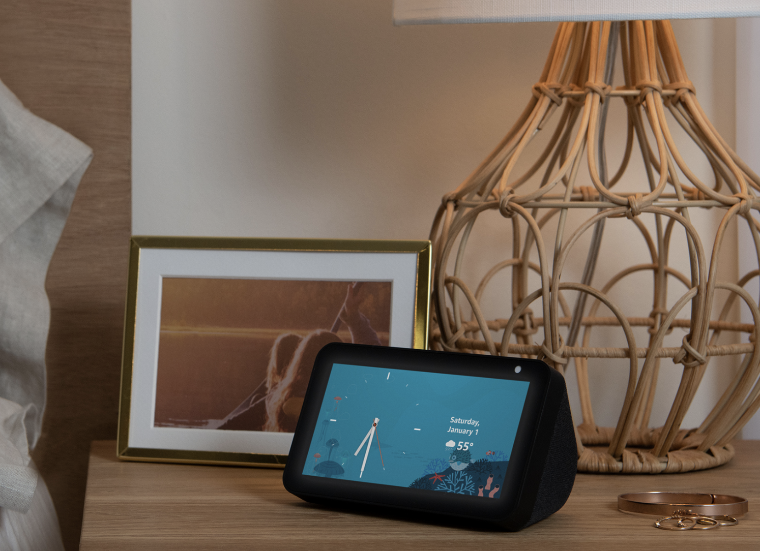 the amazon echo show 5 displaying the date and weather on a nightstand