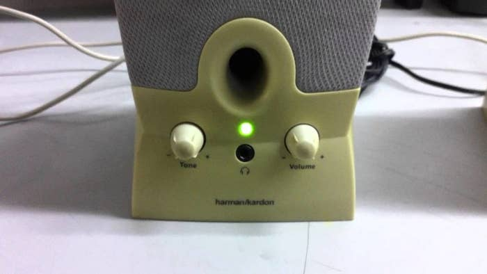 Close-up of a external computer speaker with the green light on