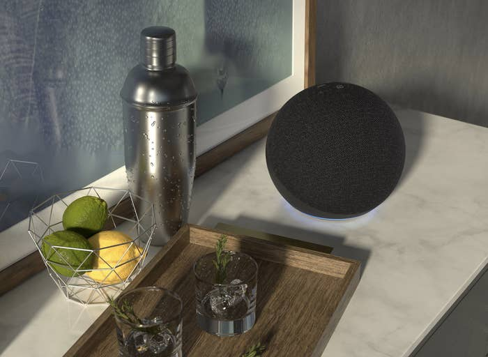 the sphere-shaped amazon echo on a counter next to a shaker and two tumblers