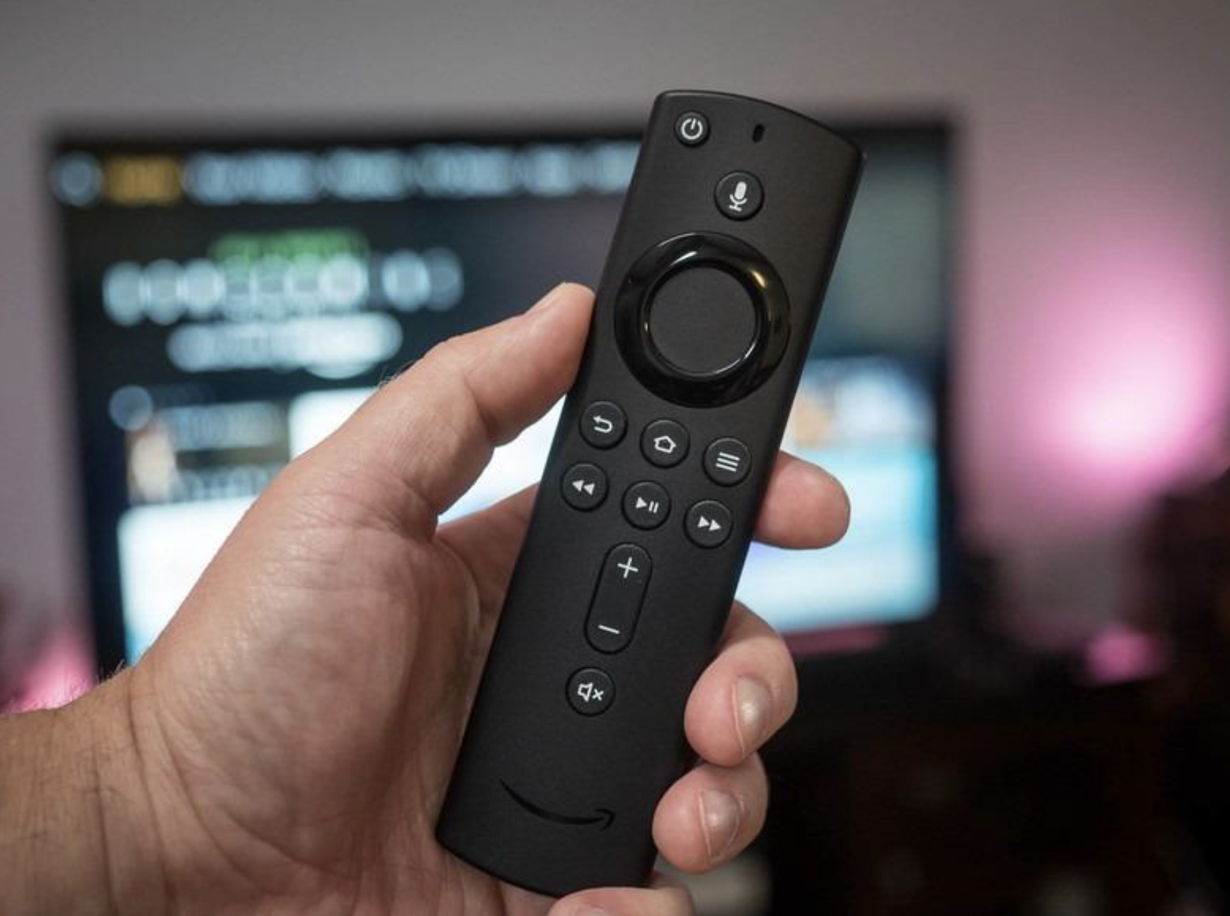 reviewer holding fire stick with tv screen in background