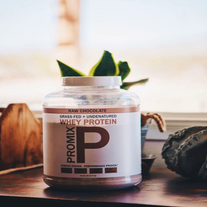 A container of protein powder sitting on a desk near a plant and window