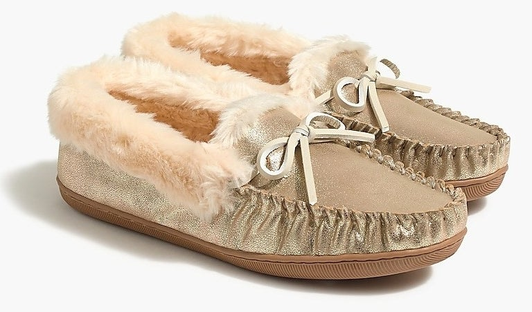 the slippers in gold faux leather with the shearling lining and faux leather bows