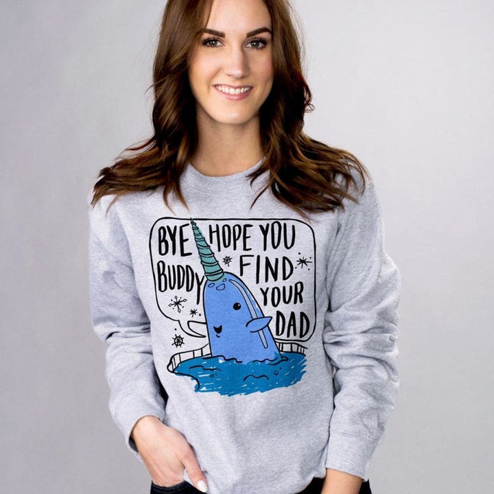 """Model wearing grey sweatshirt with illustration of a narwhal that says """"Bye Buddy, Hope you find your dad"""""""