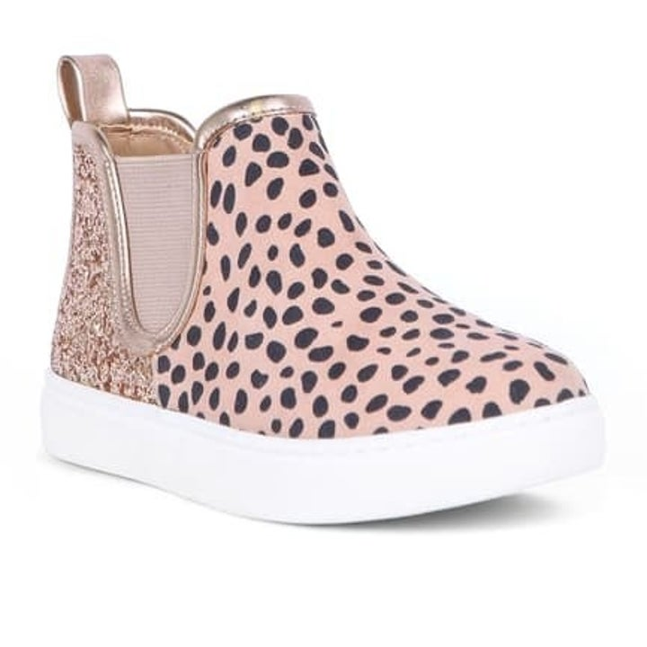pink sneaker with black dots and a gold embellishment on the back with a white sole