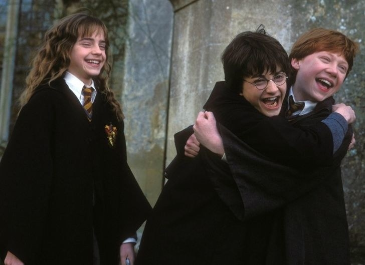 Harry and Ron embracing, while Hermione smiles and laughs in the background