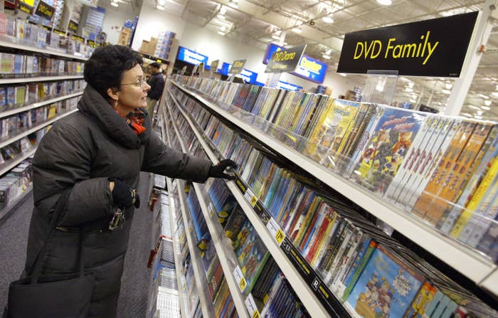 A photo of an older woman in a black winter coat looking DVDs in the DVD Family section of a Best Buy store