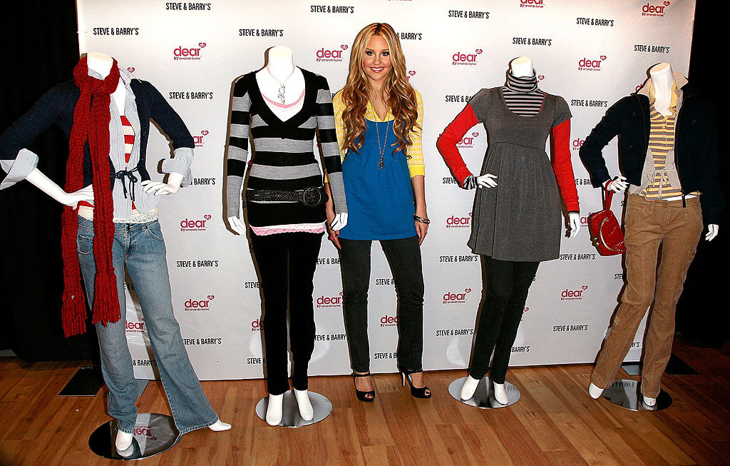 Amanda Bynes standing in between 4 mannequins dressed in her clothing inside a Steve & Barry's