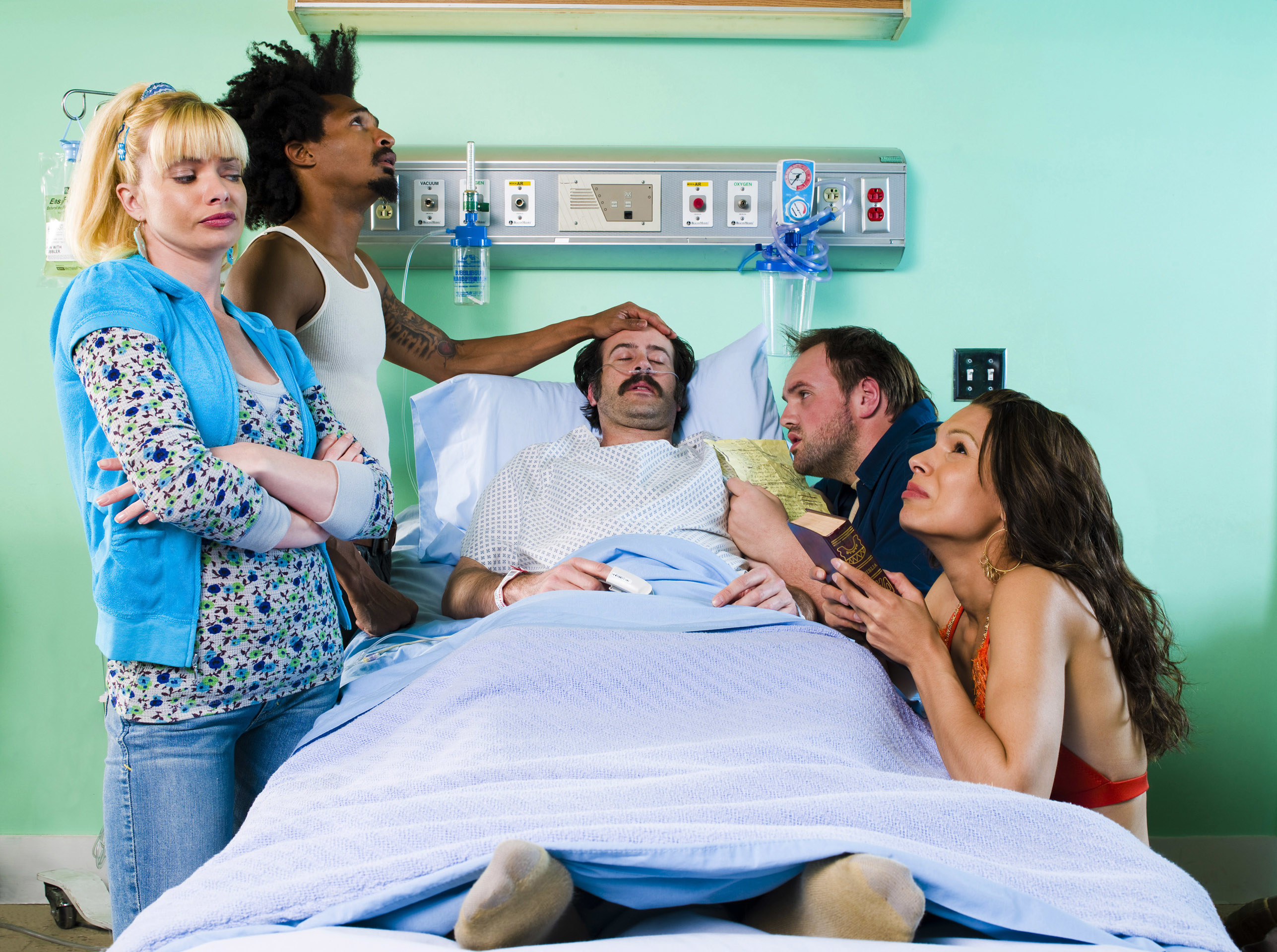 A photo of Early lying on a hospital bed surrounded by the other characters