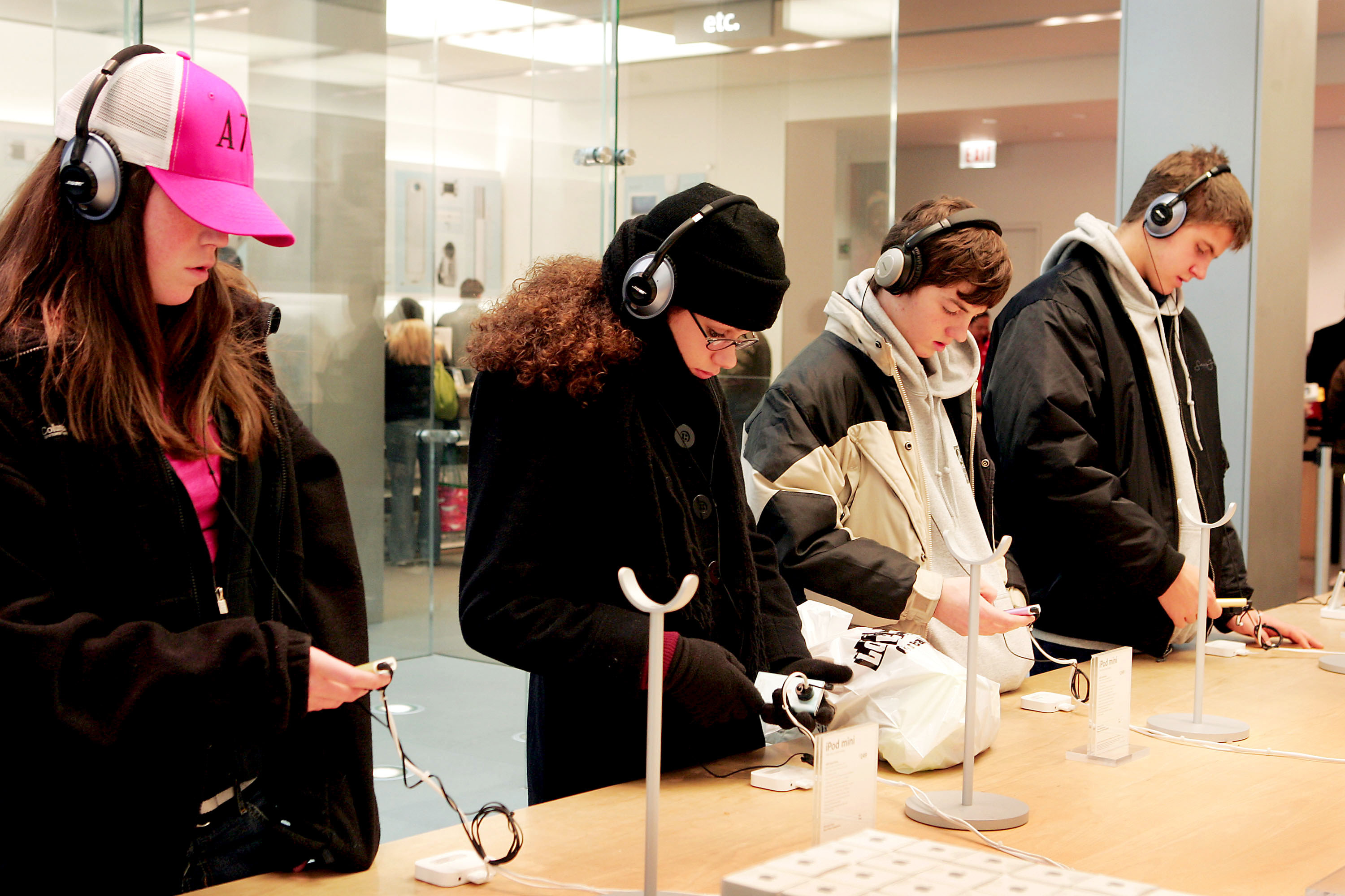 Picture of a four teens each looking at an iPod and wearing headphones inside an Apple Store