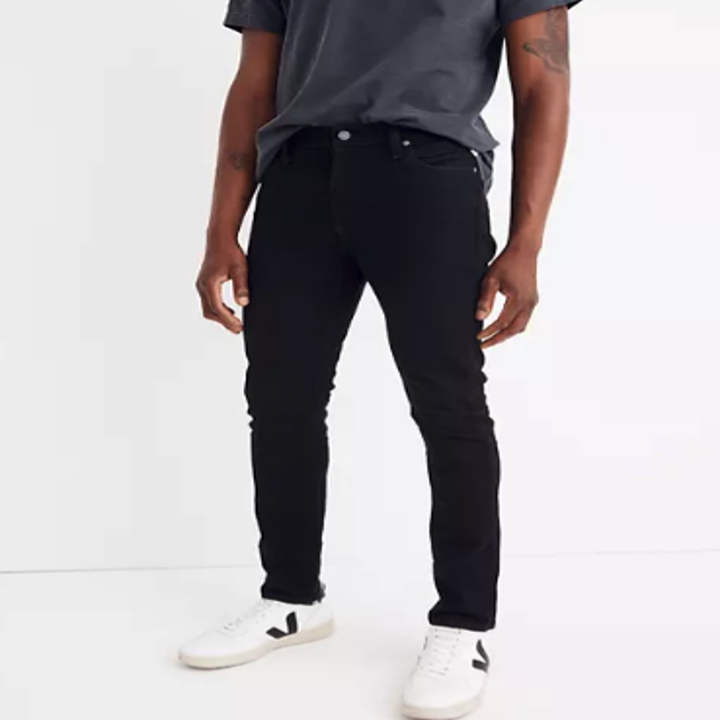 A model wearing white shoes, a grey t-shirt, and fitted black jeans