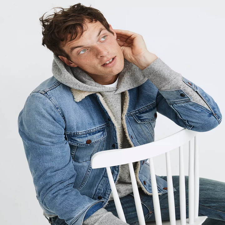 A model sitting in a white chair, touching his ear, while wearing a grey hoodie and a blue jean jacket