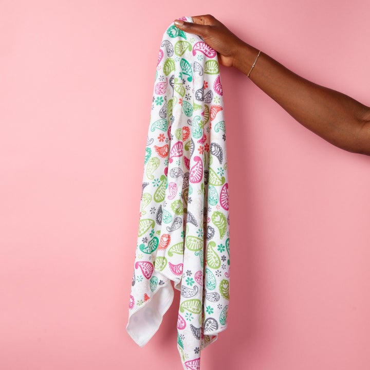 model's hand holding the towel which has a floral print on it