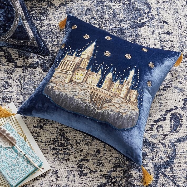 the blue velvet pillow with gold tassels and Hogwarts etched onto it