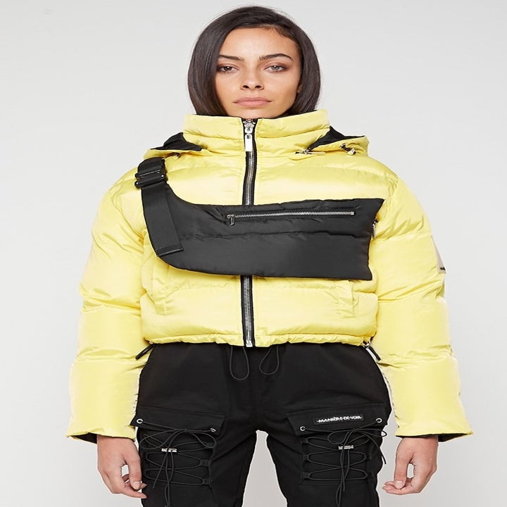 model wearing same cropped puffer jacket turned inside-out so that it's now yellow. There's still the fanny pack slung over her chest. It's black.