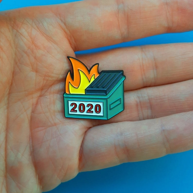 a hand holding the very small 2020 dumpster fire pin