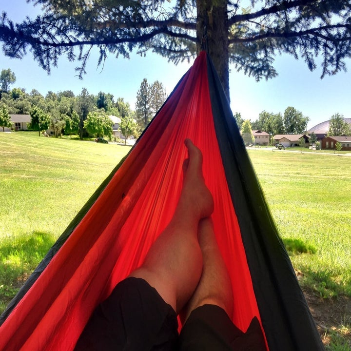 Reviewer hanging in a red hammock outside