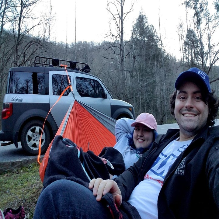 Two reviewers sitting in hammock attached to a car