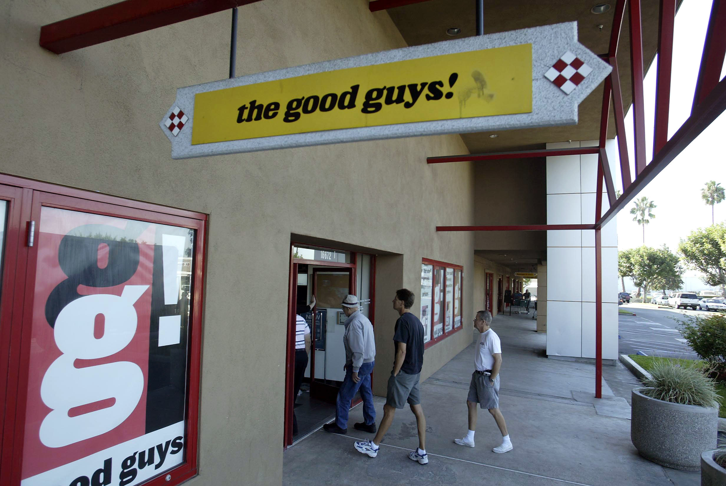 Exterior of a The Good Guys! store with shoppers walking in