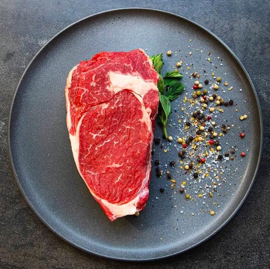 Uncooked steak on plate beside seasoning