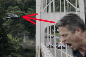Jonathon stands on the edge of a bridge while a helicopter hovers overhead nearby