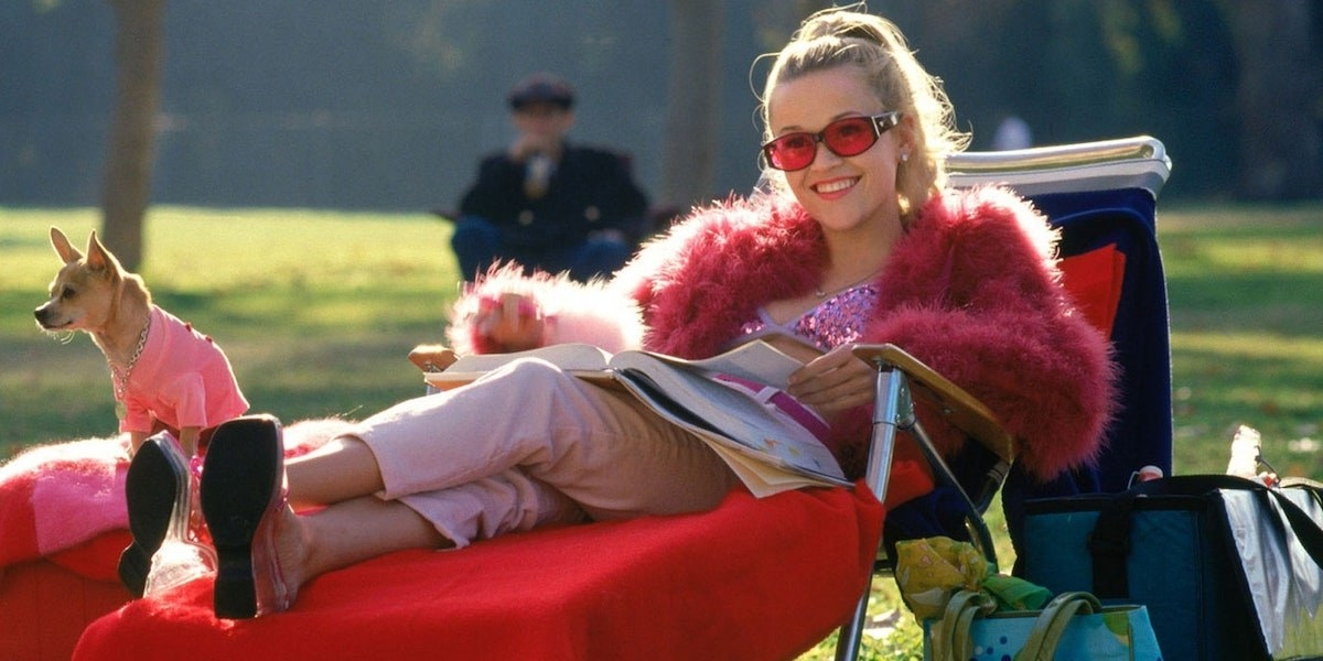 """Reese Witherspoon as Elle Woods in """"Legally Blonde""""; she is sitting on a chair outside studying"""