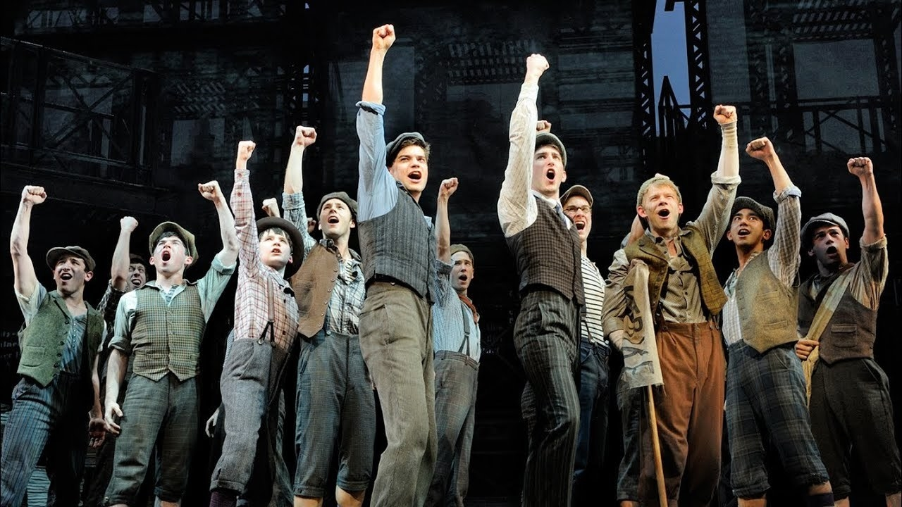 """The cast of """"Newsies"""" raising their arms up during a performance"""