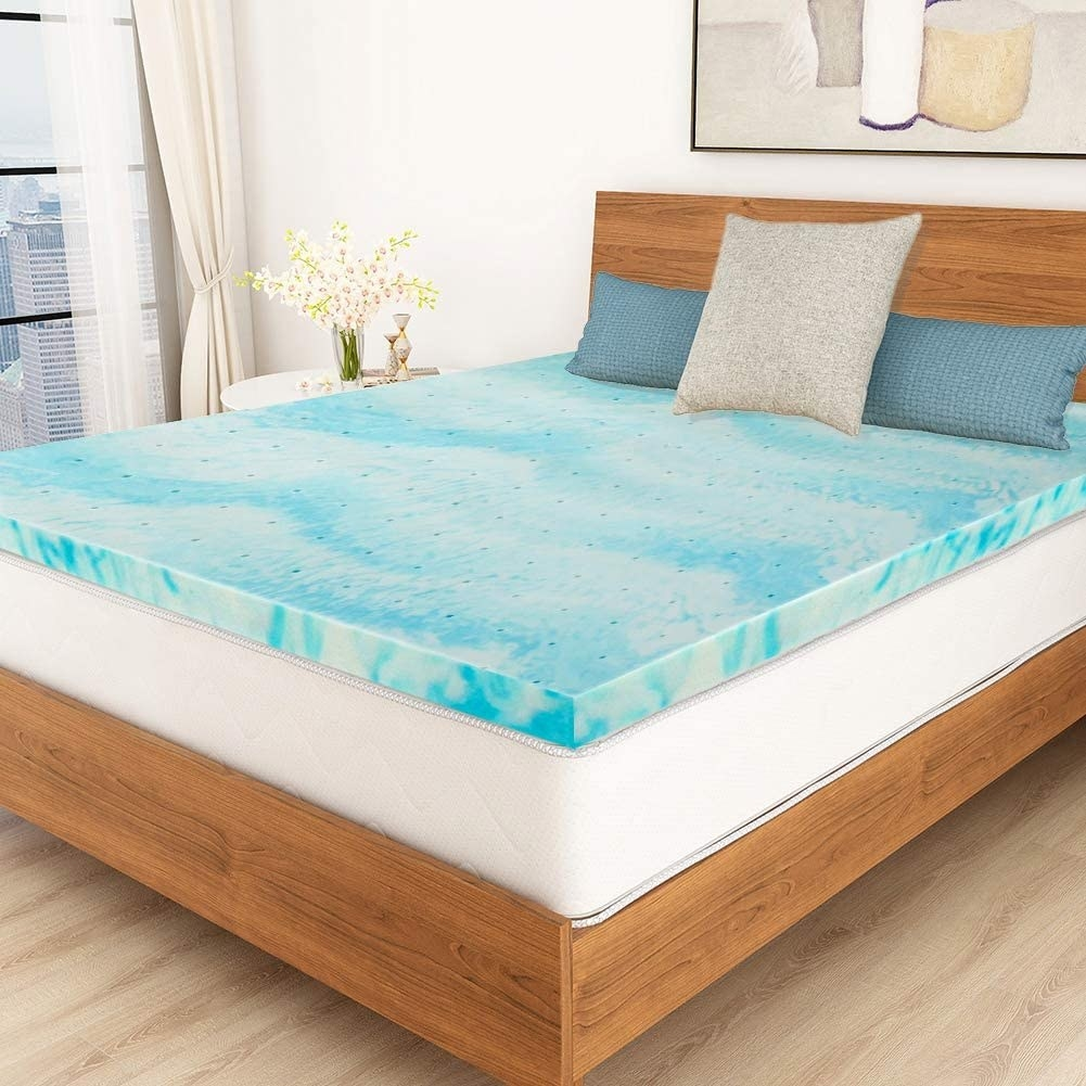 The swirly blue topper on a bed