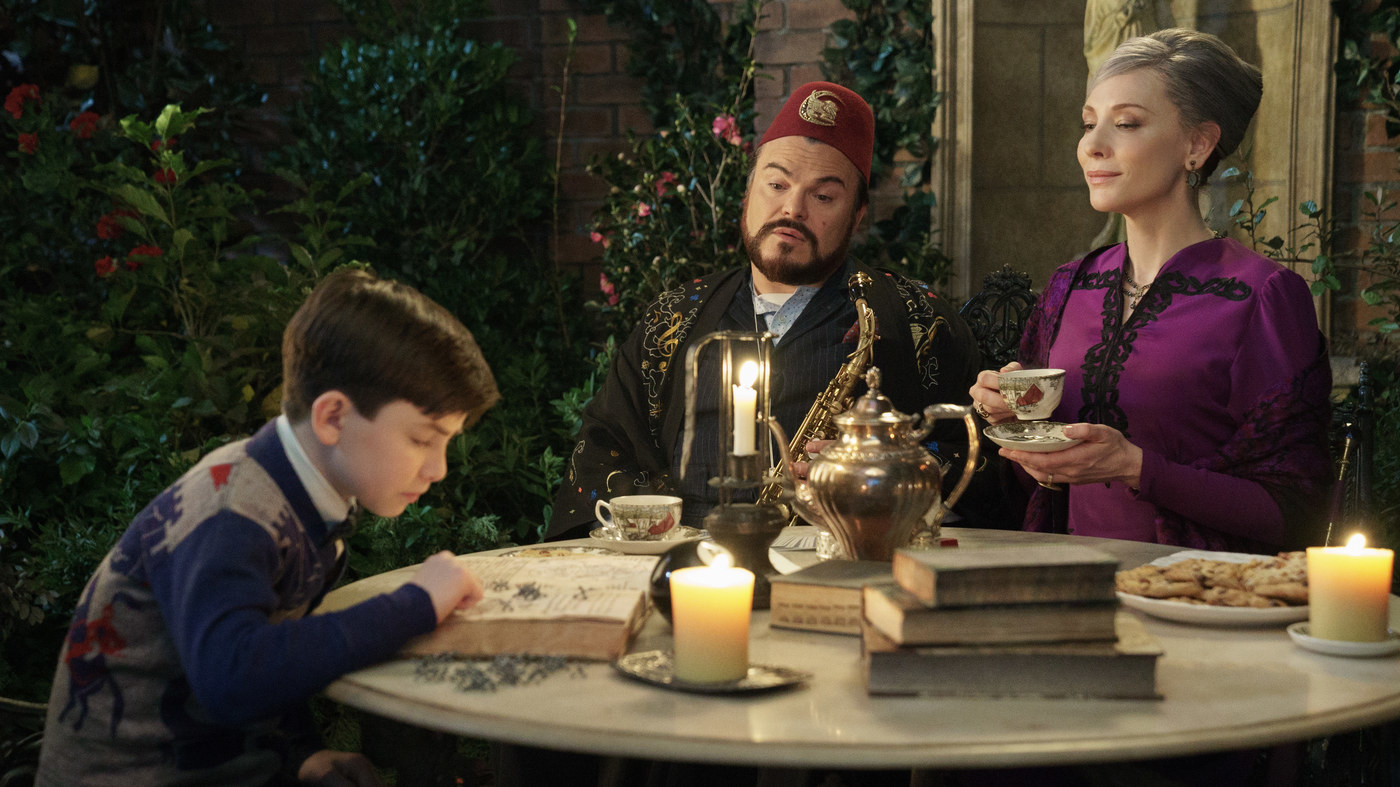 """Jack Black, Cate Blanchett and Owen Vaccaro in """"The House With A Clock In Its Wall""""; they're sitting around a table, reading books and sipping a cup of tea"""
