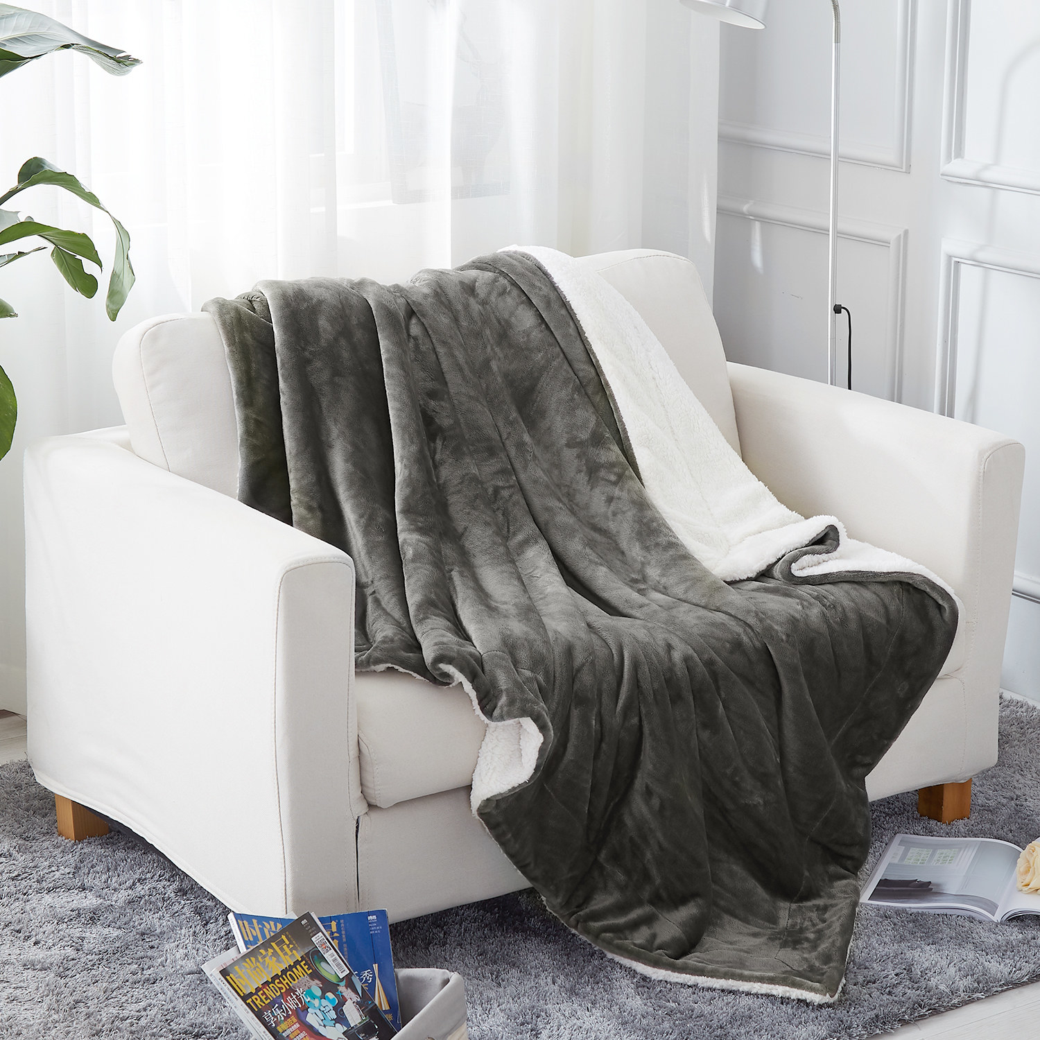 the sherpa throw in gray sprawled on top of a couch