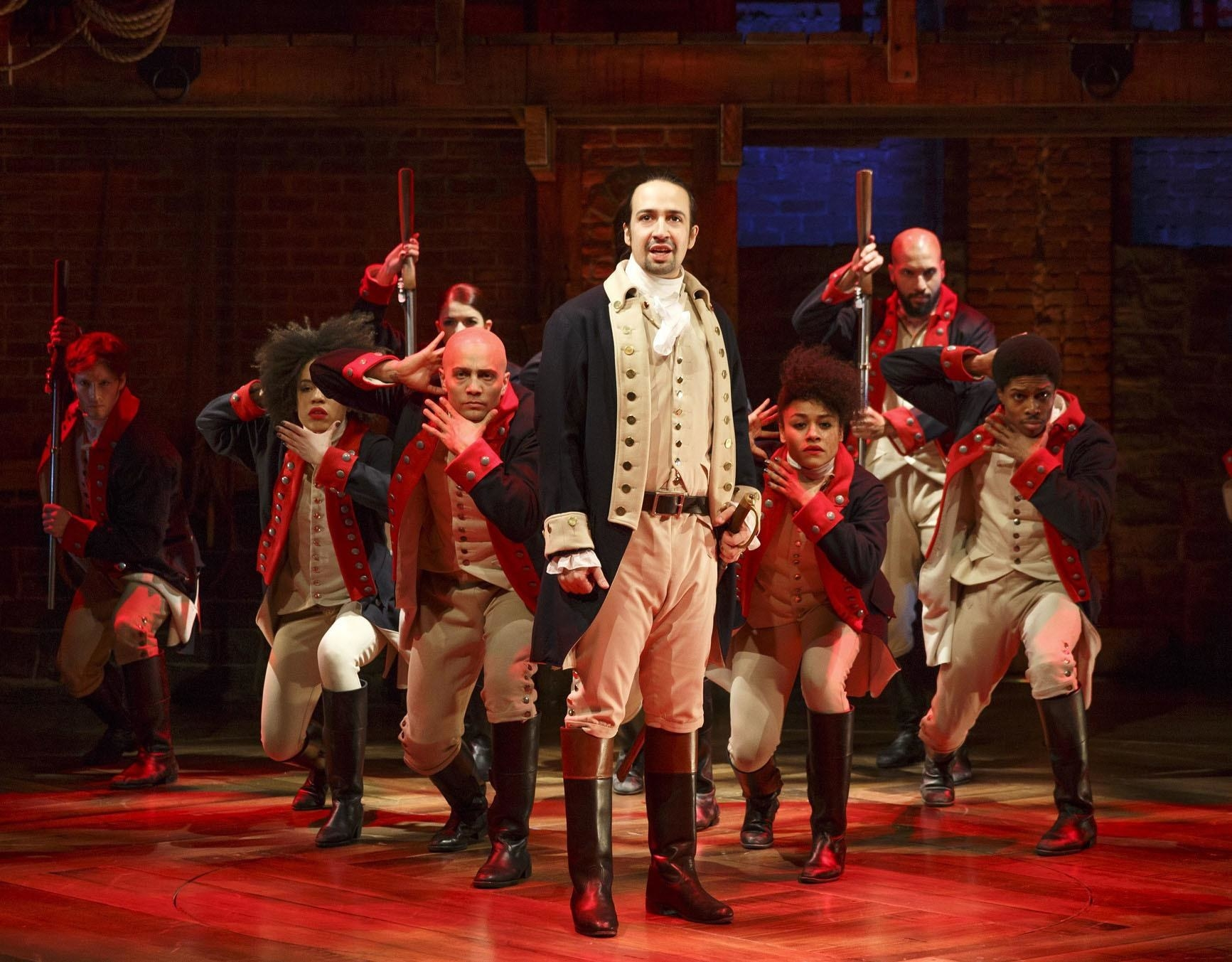 """A screenshot of the cast of """"Hamilton"""" performing"""