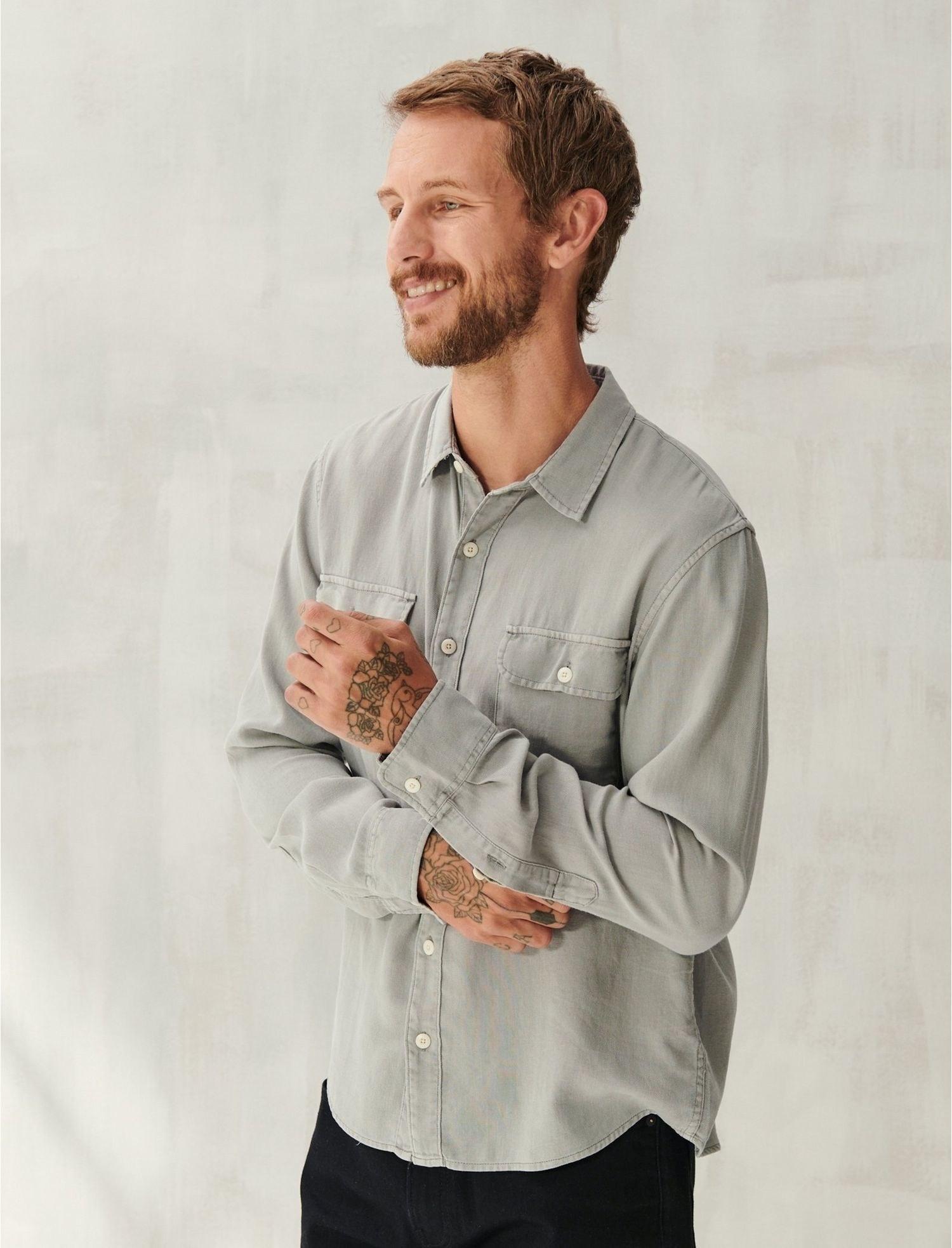 Model wearing a button-down shirt in grey