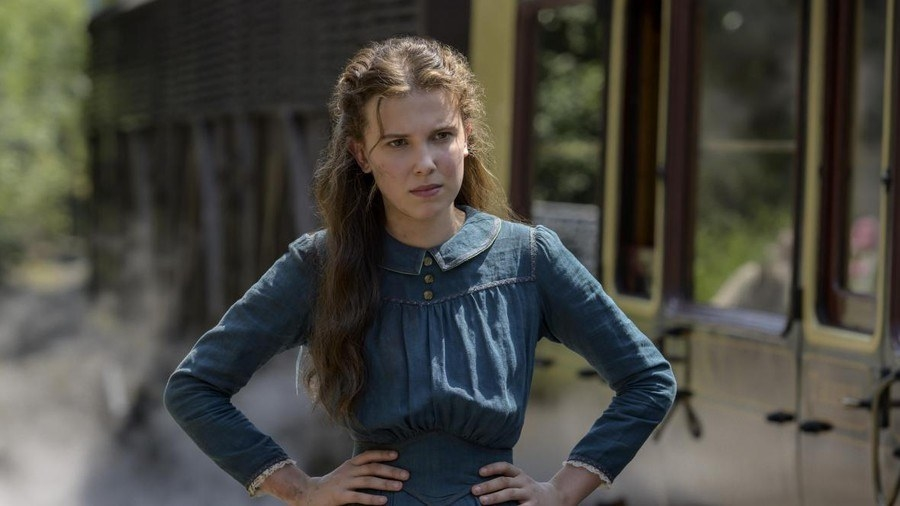 Millie Bobbie Brown as Enola Holmes; she is standing with her hands on her hips and frowning