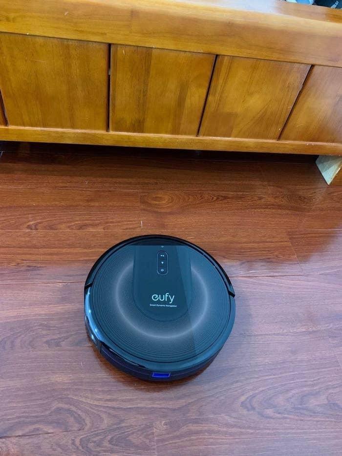 Black robot vacuum on hardwood floor