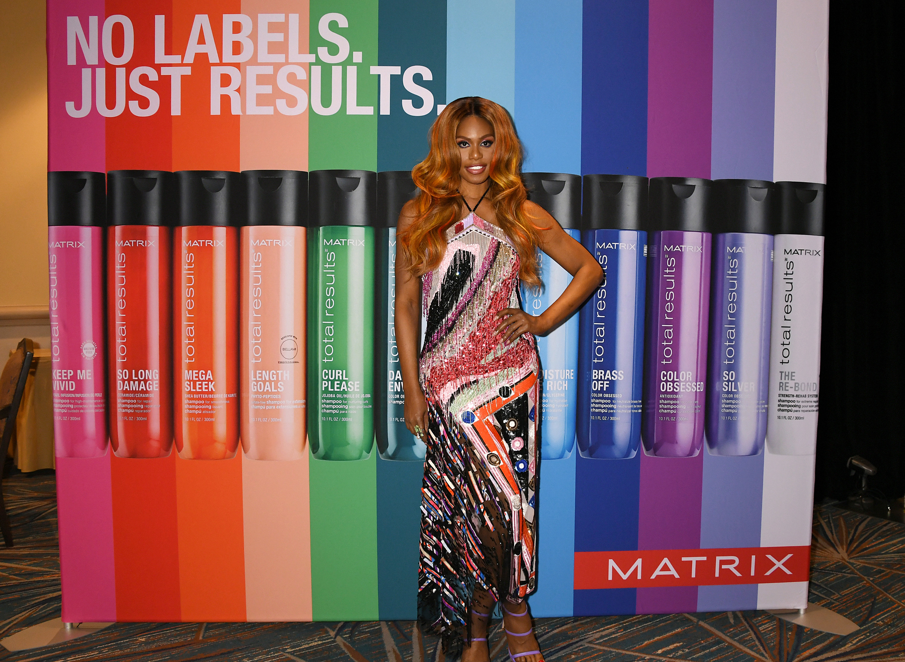 Laverne Cox wears a dress in front of a poster for Matrix-brand makeup products