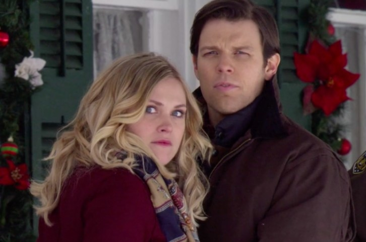 Still from Christmas Inheritance: Eliza Taylor and Jake Lacy stand close together looking at something in surprise