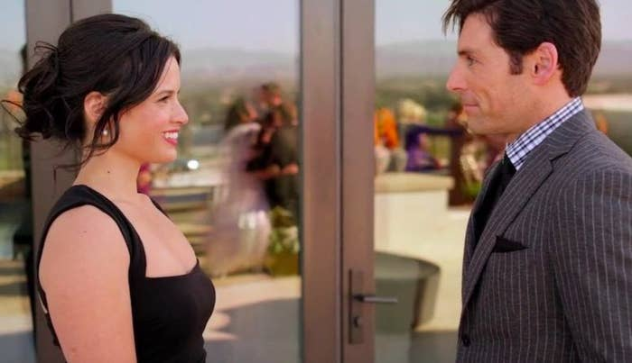 Still from Snow Bride: Katrina Law and Jordan Belfi face each other in formal clothes, smiling