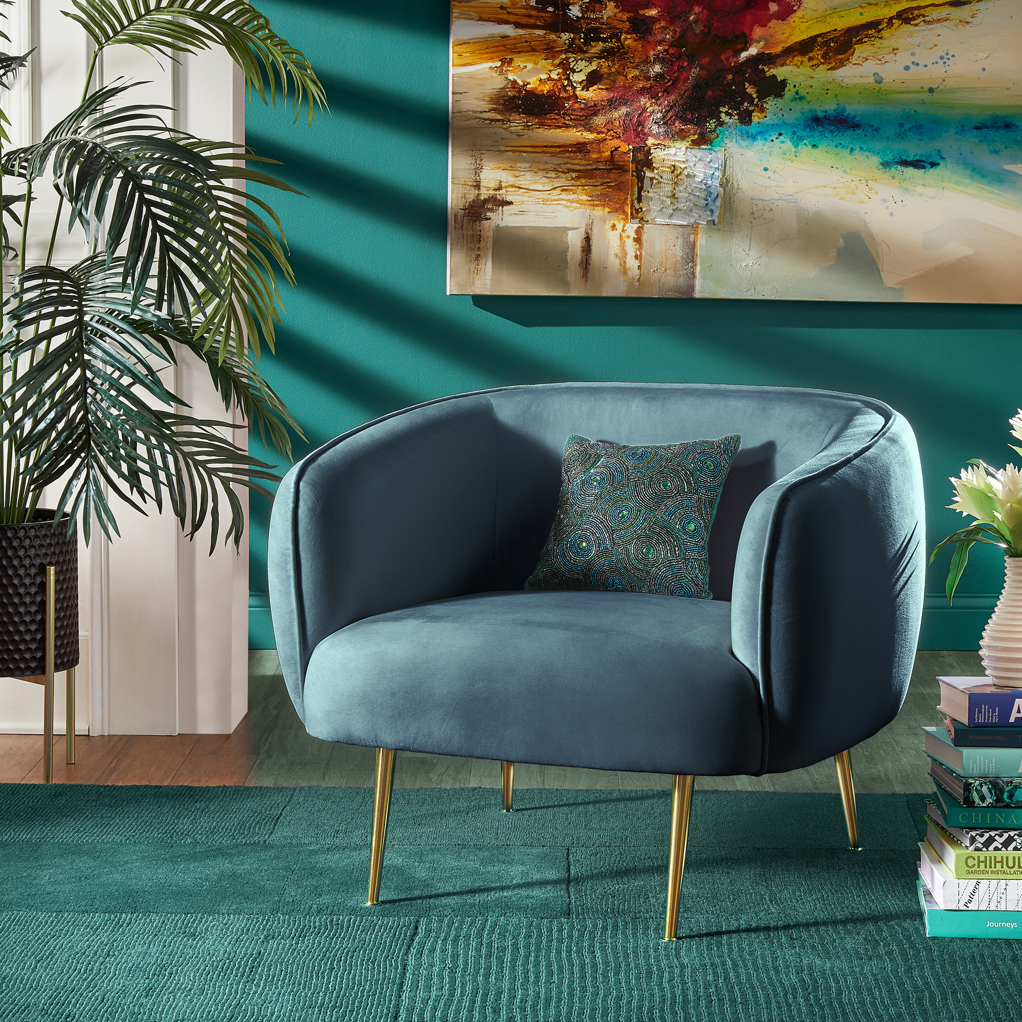 the velvet accent chair in blue with gold metal legs, books next to it, a blue rug underneath it, and a painting behind it.