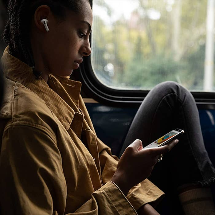 A person sitting in a car listening to music with wireless earphones