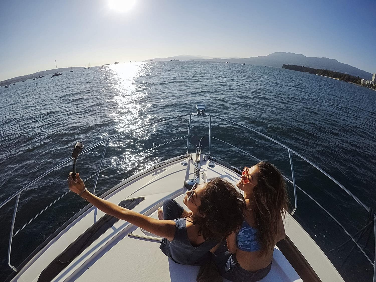 Two people sitting on a boat while one is holding a video camera up to face them