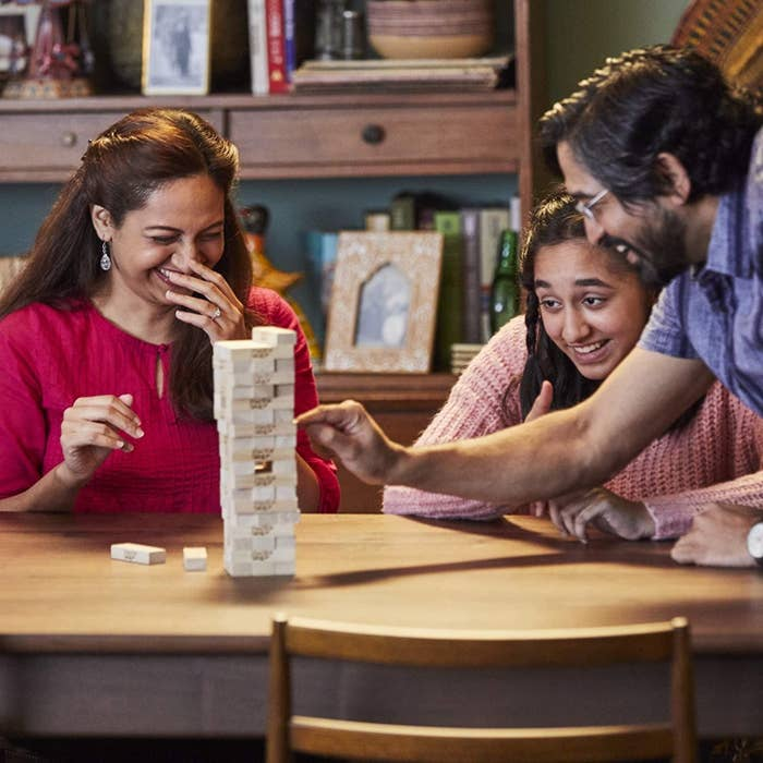 A family plays a game of Jenga