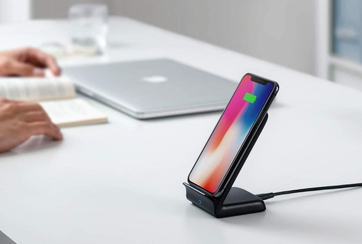 person reading book in background while phone charges on stand
