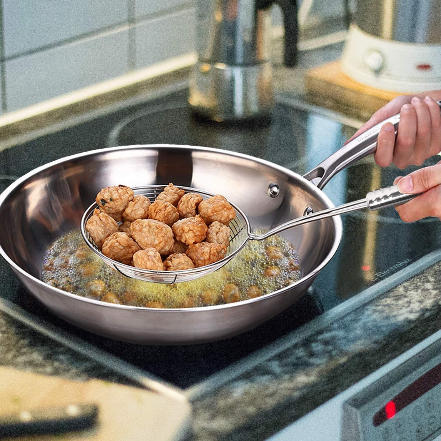 A person strains food from a pan of oil