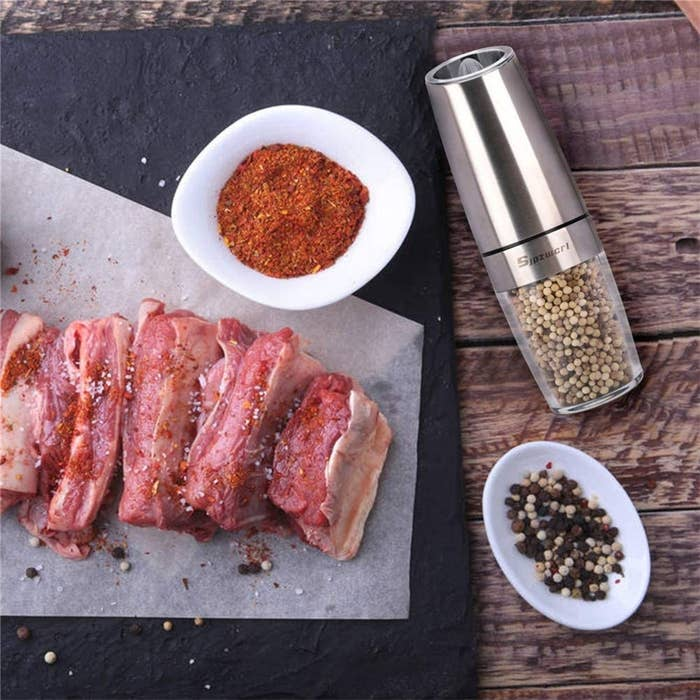 A pepper mill beside meat and spices