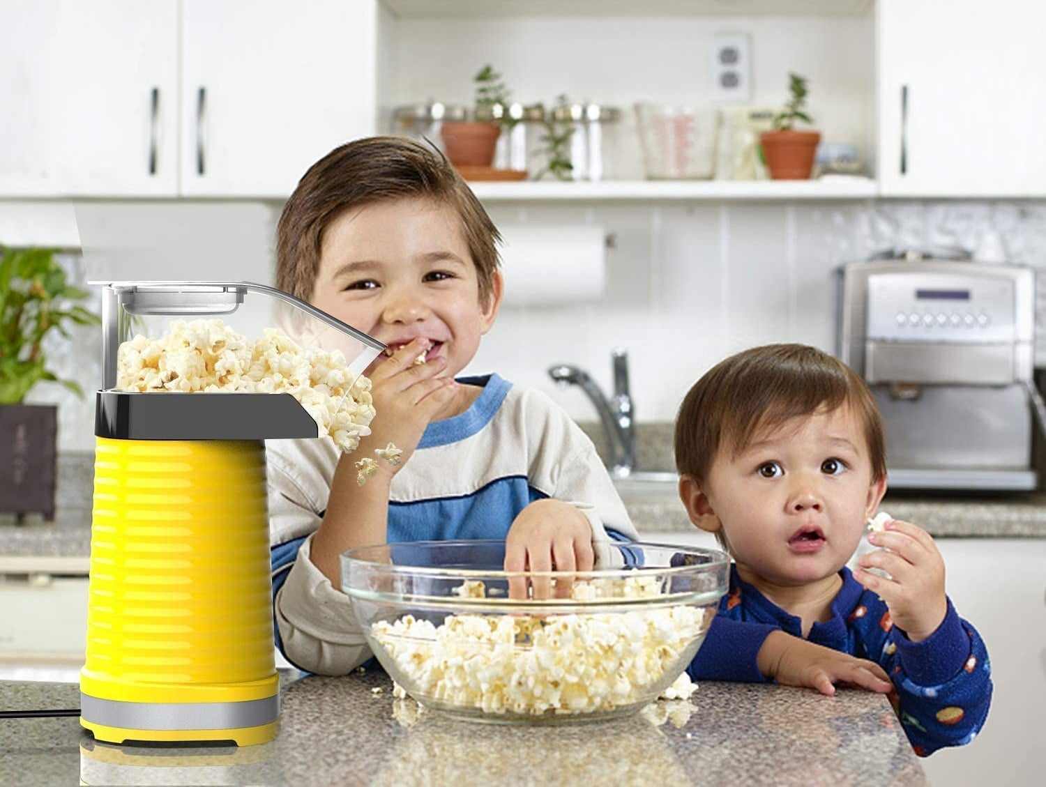 Two kids eat popcorn fresh from a popcorn maker