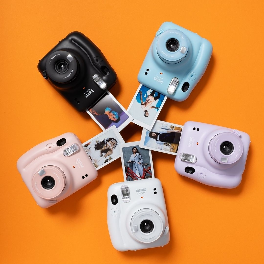 A set of five cameras arranged in a circle on a bright background