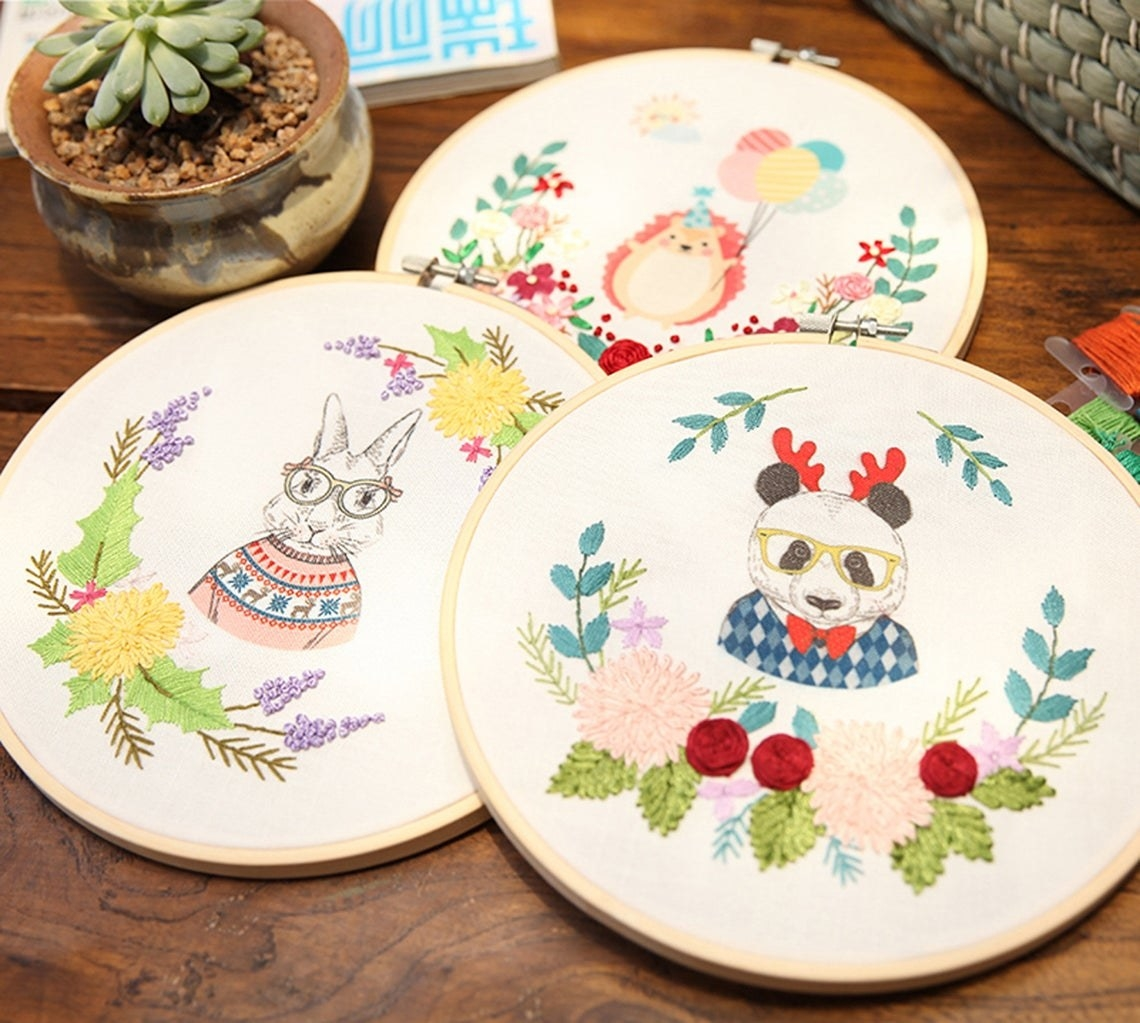 Three embroidery hoops, each with a different clothes-wearing animal and embroidered floral frames